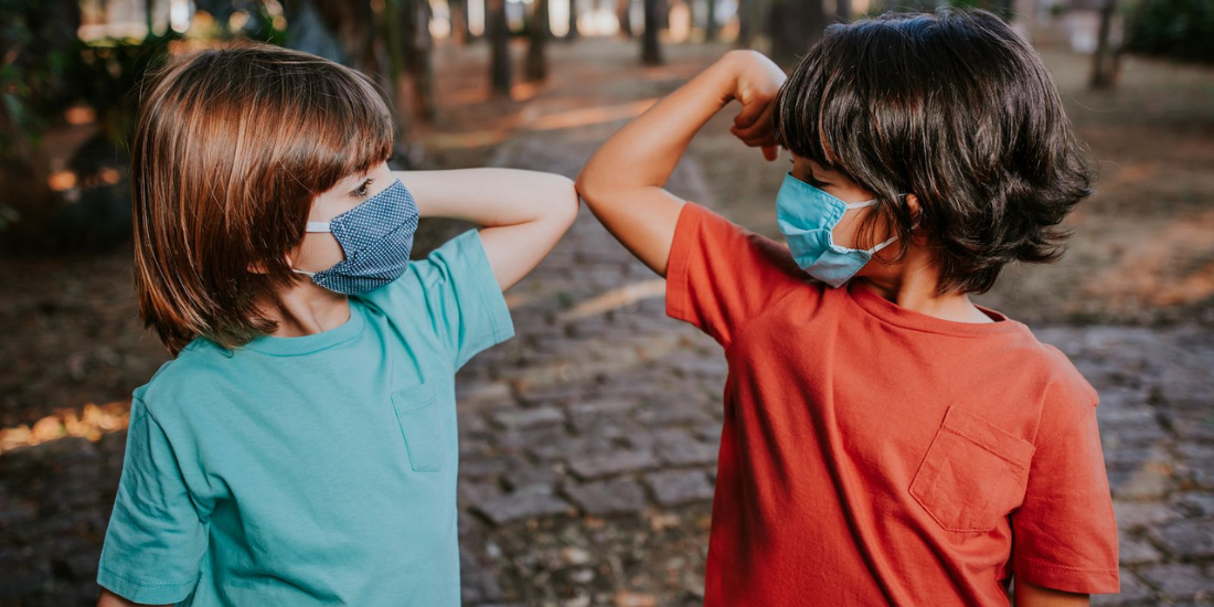 Two kids in face masks bumping elbows